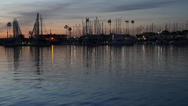 マリーナハーバーのヨットヨット。夕暮れの帆船のマスト。米国カリフォルニア州の港の夕暮れ。