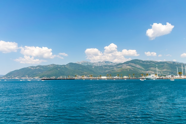 Yachts of various sizes and large vessels moored in the port of tivat.