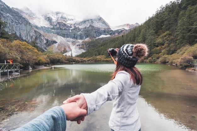 Пеший туризм молодой пары путешественника смотря красивый ландшафт на заповеднике yading, концепция образа жизни перемещения