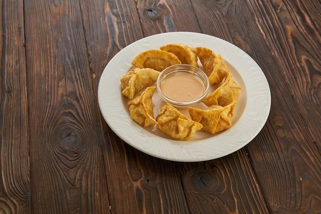 暗い木製のテーブルの上の白いプレートのソースと焼き餃子