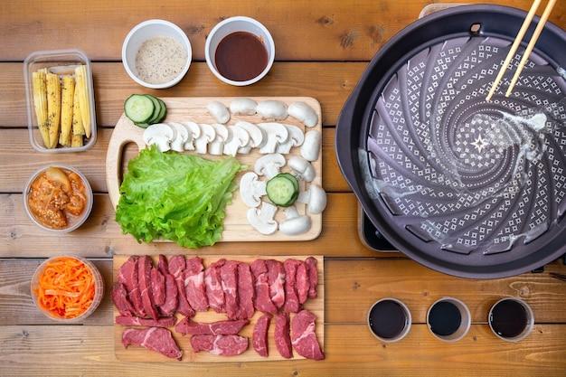 야키니쿠는 얇게 썬 쇠고기를 구운 음식입니다. 야키니쿠 가스 그릴은 친구들과 함께 그릴 음식입니다. 쇠고기 조각이있는 나무 테이블 한식 판 치칸 버섯