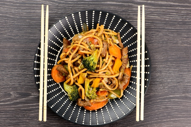 Yakisoba on a black plate on a table