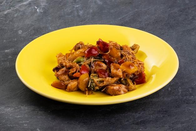 다크 슬레이트 돌에 노란색 접시에 닭고기와 야키소바.