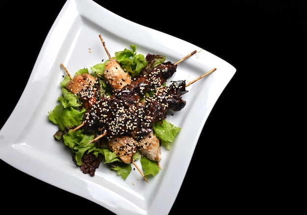 皿にゴマと焼き鳥。黒の背景に分離されたスティッククローズアップのフライドチキン肉と鶏レバー。上面図。