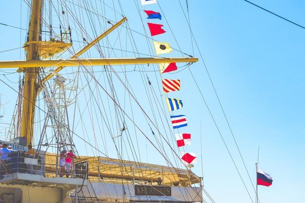 Ялта, крым - 10 августа 2018: красочные морские парусные флаги, развевающиеся на ветру от линий мачты парусника с подсветкой в ярко-синем небе от солнца.
