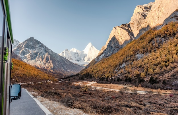 Yangmaiyong holy mountain in autumn valley on peak at yading nature reserve