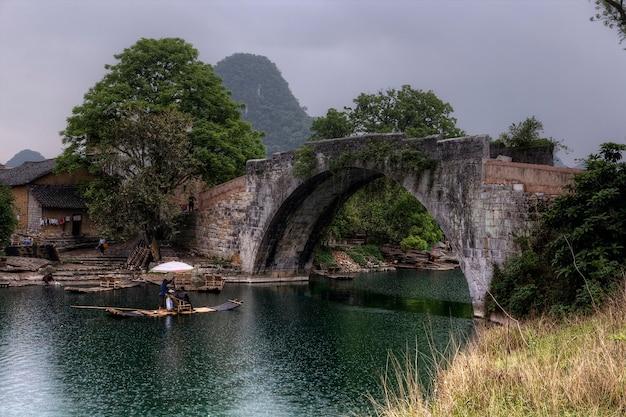 Yangshuo, guangxi, china yulong river, guilin, dragon bridge, 비오는 봄 날씨, 그림 같은 관광 도시 여행, 아름다운 하이킹 목적지 여행자의 대나무 보트 크루즈
