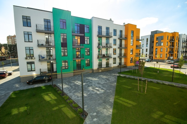 Yard between residential apartment buildings with green grass lawns and modern flat housing. real estate development.