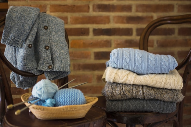 Пряжа и теплая одежда на стульях