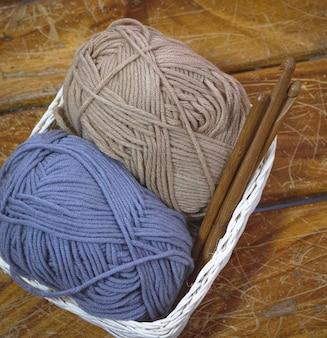 나무 판자에 짠 바구니에 실 공과 크로 셰 뜨개질 후크를 넣습니다.