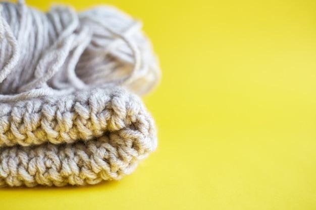 毛糸のボールとニットの帽子が黄色いテーブルを照らしてクローズアップ