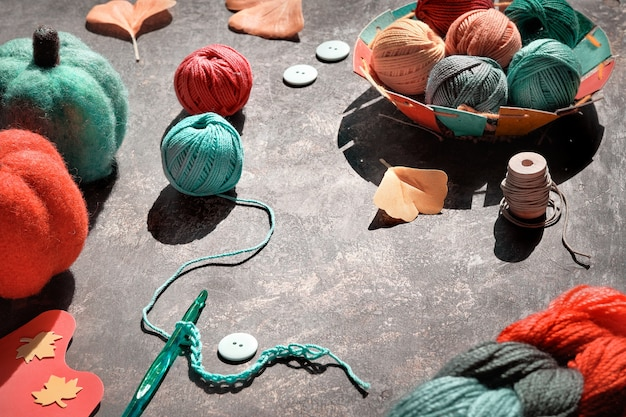 Шарики из пряжи, крючок с ниткой, пуговицы, декоративные тыквы