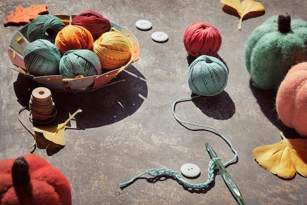 毛糸ボール、糸付きかぎ針編みフック、装飾的なフェルトカボチャ、イチョウの葉