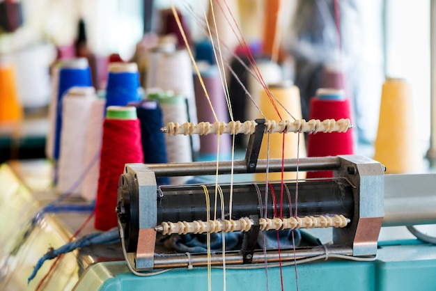 Yarn feeder with threaded wool of assorted colors on knitting machine at a knitwear factory in close up detail