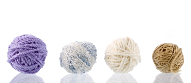 Yarn for handwork and knitting. set on a white surface with reflection.