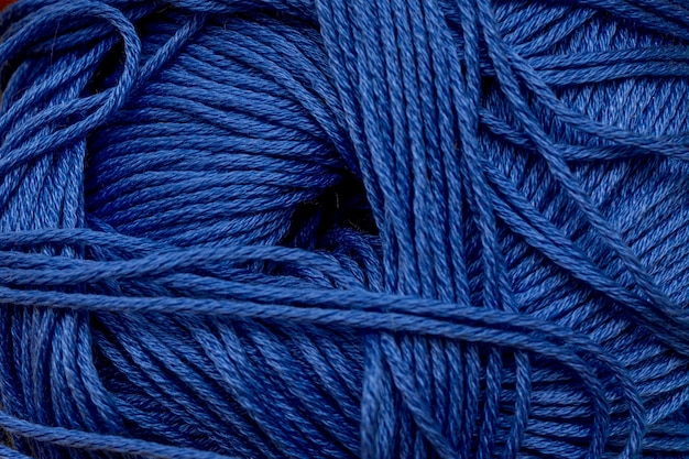 Yarn for knitting close-up blue background.