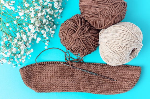 Yarn and a knitting hook on a blue background