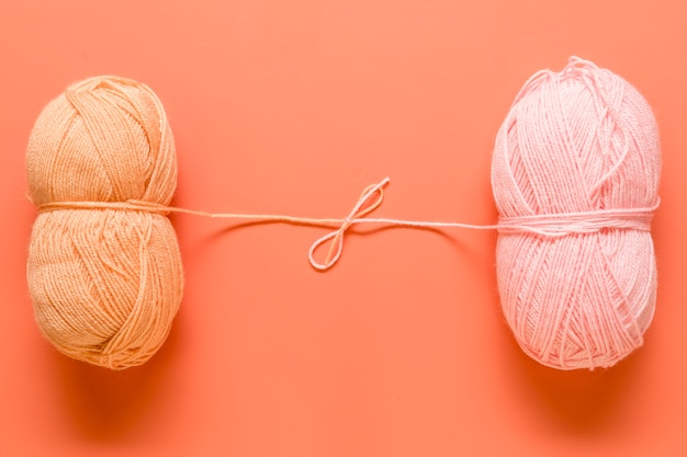 Yarn for knitting tied in bow on orange background