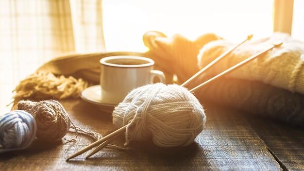Yarn and needles near hot beverage