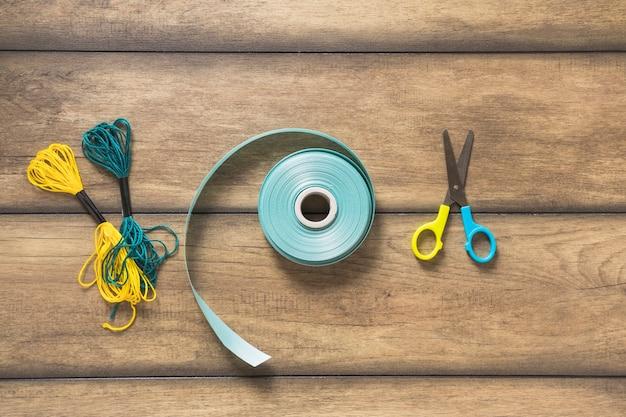 Yarn thread; ribbon and scissor on wooden backdrop