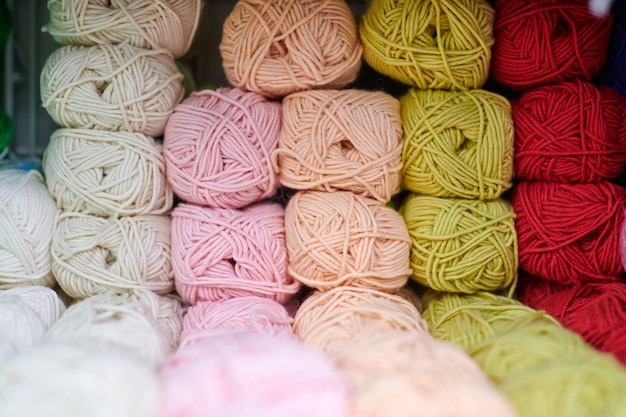 Yarns or balls of wool on shelves in store for knitting and needlework, close up. accessories for haberdashery in fabric store shelves