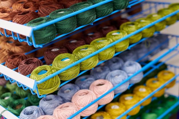 뜨개질과 바느질 작업을 위해 선반에 있는 털실이나 양모 공. 패브릭 매장 선반의 잡화 액세서리. 여러 그림, 배경입니다.