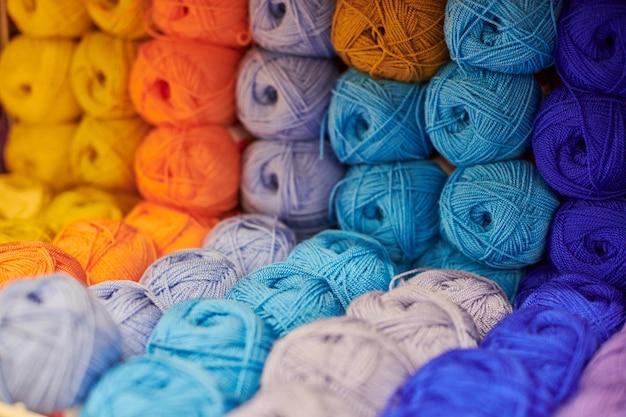 뜨개질과 바느질을 위해 선반에 있는 털실이나 양모 공을 닫습니다. 패브릭 매장 선반의 잡화 액세서리. 여러 그림, 배경입니다.