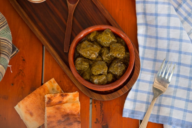 Yarpag dolmasi, yaprak sarmasi, green grape leaves stuffed with rice and meat in pottery bowl