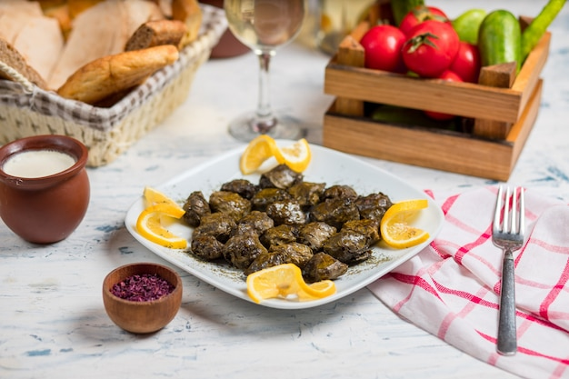 Yarpaq dolmasi, yaprak sarmasi, grape green leaves filled, stuffed with meat and rice, served with lemon