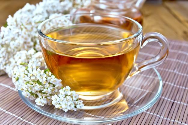 Чай тысячелистник в стеклянной чашке и чайнике, свежие цветы тысячелистника на фоне бамбуковых досок и салфек.