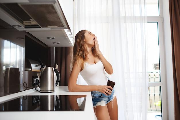あくびの美しい少女は、キッチンでコーヒーを作る