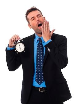 Зевающий бизнесмен, держащий будильник