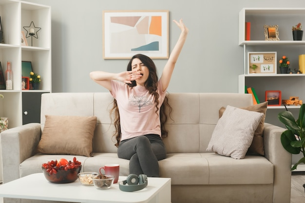 Yawning covered mouth with hand young girl sitting on sofa behind coffee table in living room