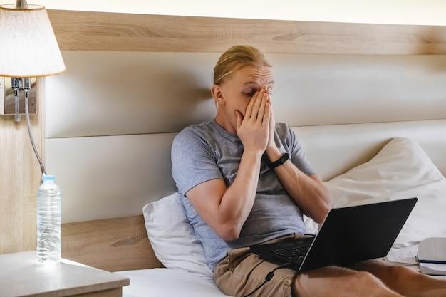 Yawning freelancer working online on hotel bed