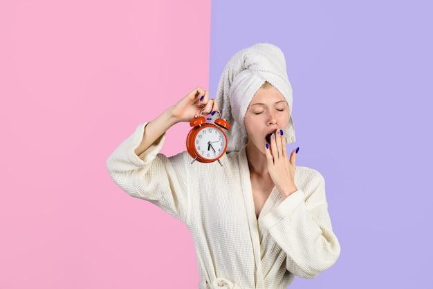 Yawning girl with alarm clock people sleeping and bedtime concept sleepy woman in bathrobe with