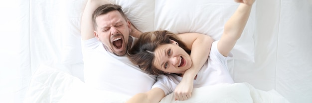 Yawning happy man and woman lie on large white bed comfortable sleep concept