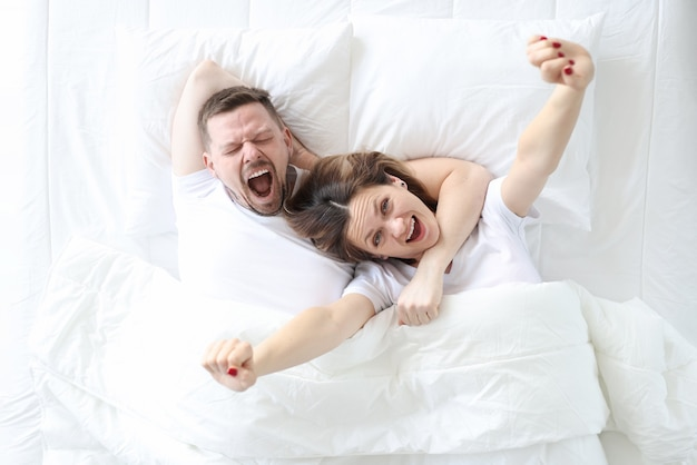 Yawning happy man and woman lie on large white bed