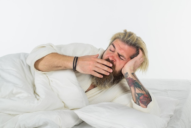 Yawning man in bed bearded man in bed morning and wake up nap man sleeping sweet dreams