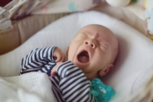 あくびをしている生まれたばかりの赤ちゃんがベッドに横たわっています