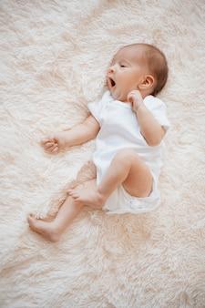 Зевающий новорожденный ребенок лежит на мягком одеяле
