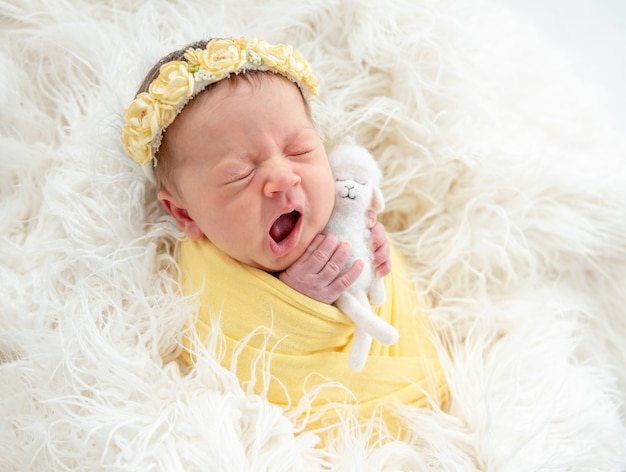 Yawning newborn holding toy