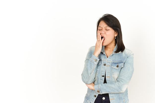 白い背景で隔離のジーンズジャケットと黒のシャツを着て美しいアジアの女性のあくび