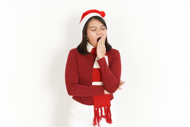 赤いタートルネックと白い背景で隔離のサンタ帽子を身に着けている美しいアジアの女性のあくび