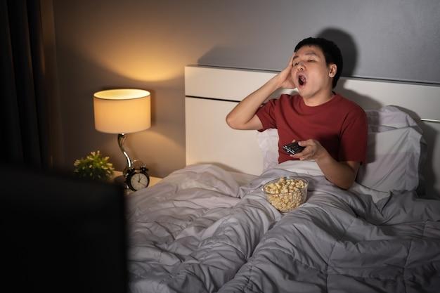 Yawning sleepy man man watching tv movie on a bed at night