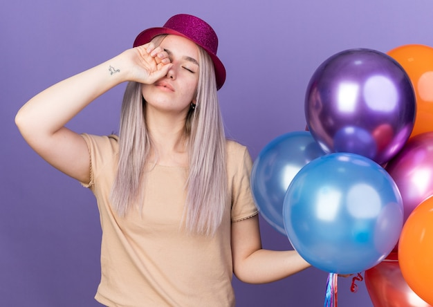 Yawning with closed eyes young beautiful girl wearing party hat holding balloons wiping eye with hand isolated on blue wall