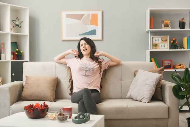 Yawning with closed eyes young girl sitting on sofa behind coffee table in living room