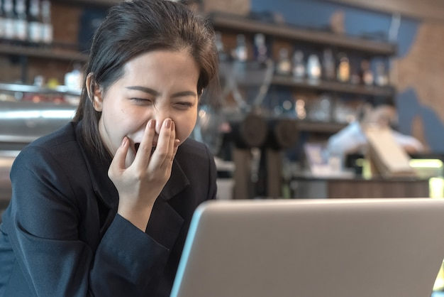 Yawning woman while working with laptop in coffee shop