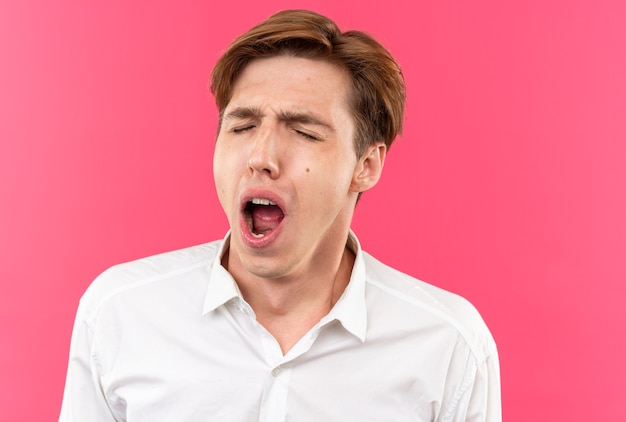 Yawning young handsome guy wearing white shirt isolated on pink wall