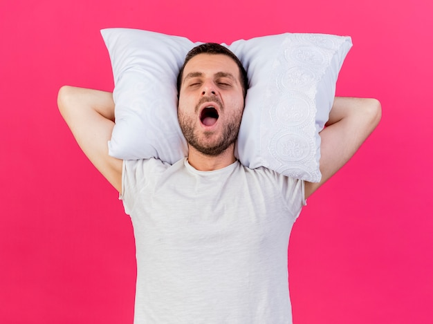 Yawning young ill man holding pillow behind head isolated on pink