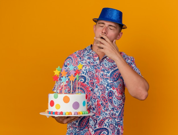 Yawning young party guy wearing blue hat holding cake isolated on orange